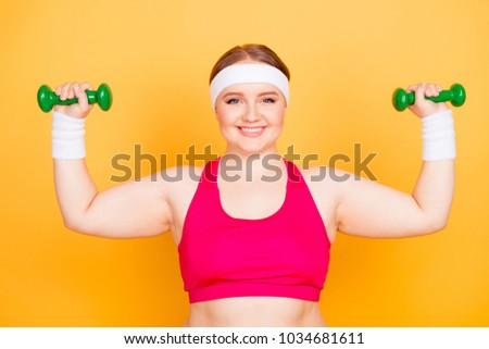 I'm capable of everything! Close up portrait of cheerful with toothy smile plump woman, she is training her arms using little green dumbbells, isolated on bright yellow background
