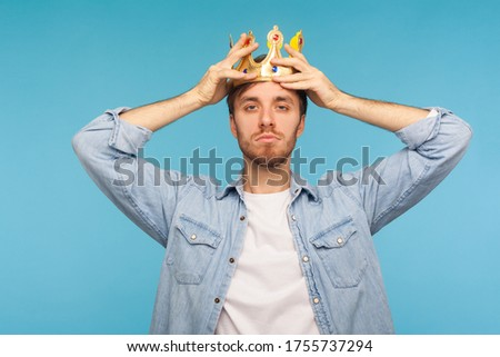 I'm ceo! Portrait of worker man wearing golden crown, imagining promotion at work to position of top manager or boss, looking with arrogance, privileged status. studio shot isolated on blue background Stock fotó ©