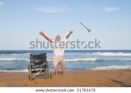 I'm free. senior man get up from wheelchair and throw away his walking cane - stock photo