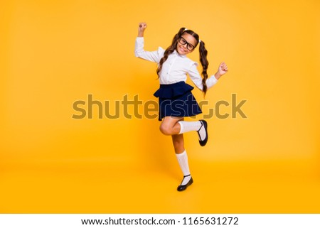 I'm happy because I'm going back to school! Full length, legs, body, size portrait of small girl isolated on bright yellow background stands on one leg raised her hands up Stock fotó ©