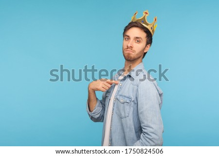 I'm king! Portrait of ambitious man wearing golden crown and pointing himself, looking with arrogance, declaring his authority, superior privileged status. studio shot isolated on blue background Foto d'archivio ©