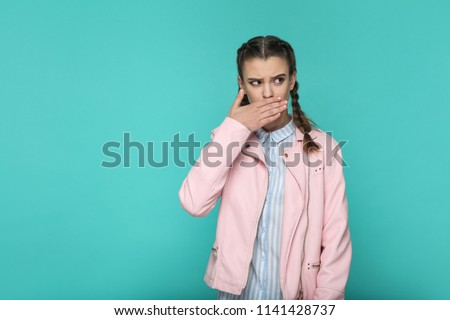 I'm silent. portrait of beautiful cute girl standing with makeup and brown pigtail hairstyle in striped light blue shirt pink jacket. indoor, studio shot isolated on blue or green background.