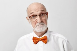 I'm very impressed. Emotional unshaven European elderly retired man wearing glasses and bow tie, raising eyebrows, astonished with impressive news. Amazement, surprise and astonishment concept