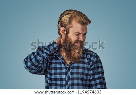 I need a massage. Frustrated man holding hand on his neck, having pain on the back. Hipster male with beard in blue plaid checkered shirt  Isolated on blue studio Background. Negative face expression.