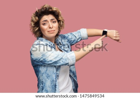 I need more time. Portrait of young pleased woman with curly hairstyle in casual blue shirt standing and pointing at her smart watch and want more time. indoor studio shot, isolated on pink background