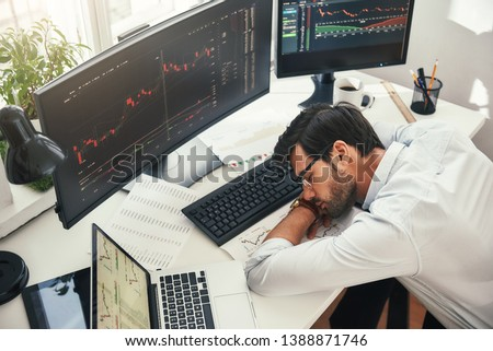 I need to relax. Tired young bearded trader in formal wear sleeping on the desk while working late in his modern office
