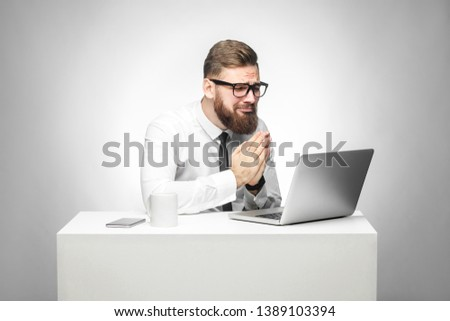 I need your help! Portrait of hopeful bearded young manager in white shirt and black tie are sitting in office and talking with friend thought skype and pleased for helping him in work task. Isolated