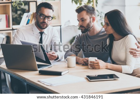 I need your signature here. Confident young man in shirt and tie holding some document and pointing it while sitting together with young couple at the desk in office  #431846191