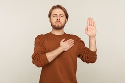 I promise to tell truth! Portrait of honest responsible bearded man in sweatshirt standing raising hand and saying swear, making loyalty oath, pledging allegiance. indoor studio shot, gray background