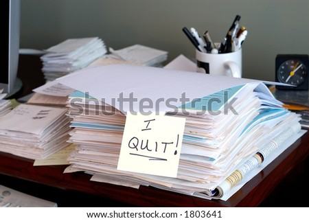 I Quit - A sticky note that says I QUIT on a pile of unfinished work in the office.