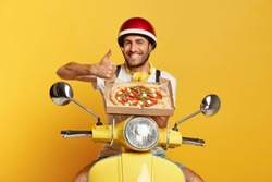 I recommend eat this delicious pizza! Cheerful busy man courier delivers appetizing fast food in cardboard container, keeps thumb up, shows like gesture, drives moped, transports for customers.