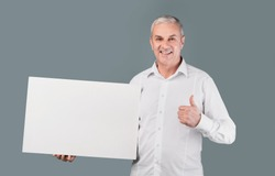 I Recommend. Smiling Senior Man Holding Blank Placard With Copy Space, Showing Thumbs Up, Gray Studio Wall