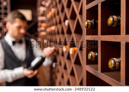 I recommend this wine. Confident male sommelier showing wine bottle and smiling while standing near the wine shelf