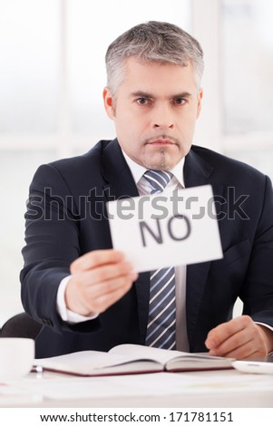 I said no! Serious senior man in formalwear holding a paper with no sign on it while sitting at her working place