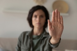 I said stop it. Blurred portrait of young lady looking at camera extending hand forward saying no enough to abuse family violence abortion. Focus on female palm close up raised in prohibiting gesture