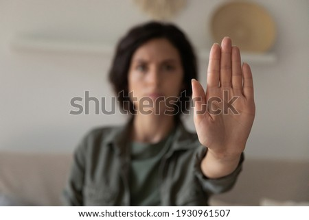 I said stop it. Blurred portrait of young lady looking at camera extending hand forward saying no enough to abuse family violence abortion. Focus on female palm close up raised in prohibiting gesture Сток-фото ©