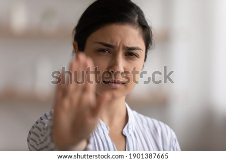 I say enough. Portrait of desperate indian woman showing stop gesture to any manifestations of racial gender discrimination. Strong hindu lady look at camera defend female right for free determination Stockfoto ©