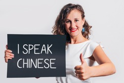 I speak Chinese phrase inscription on a board held by a smiling gesturing woman.