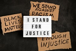 I stand for justice text on light box and other anti racism slogans over dark background