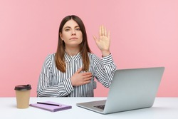 I swear! Honest dedicated woman office worker raising hand to give promise sitting at workplace, taking oath with trustworthy faithful expression. Indoor studio shot isolated on pink background