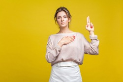 I swear! Portrait of faithful serious woman with fair hair in casual blouse standing, with hand on chest and fingers up, swearing taking oath, promise. indoor studio shot isolated on yellow background