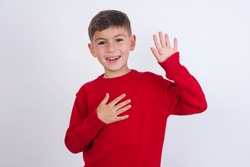 I swear, promise you not regret. Portrait of sincere Cute Caucasian kid boy wearing red knitted sweater against white wall raising one arm and hold hand on heart as give oath, telling truth.