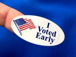 I voted early sticker on woman's finger with blue fabric background