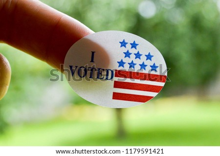 I voted sticker on a woman's finger #1179591421