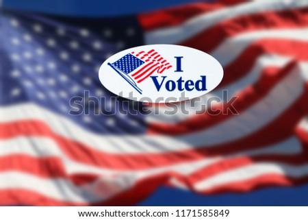 I Voted sticker on the US flag back ground.
