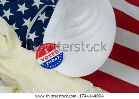 I Voted Today sticker with N95 mask and latex gloves on United States flag background concerning voting in the midst of the Covid 19 pandemic Stock photo ©
