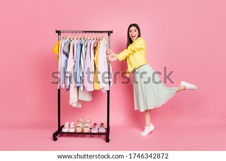 I want all this. Full length photo of pretty lady showroom fashion collection choosing clothes wear trend yellow leather jacket long skirt shoes isolated pastel pink color background