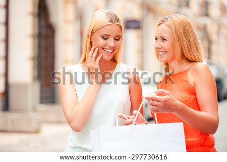 I want you to have it. Happy mature woman holding shopping bag while her daughter looking inside of it and smiling