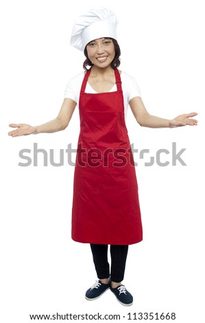 I welcome you my guests. Asian female chef posing with arms wide spread, grand welcome. - stock photo
