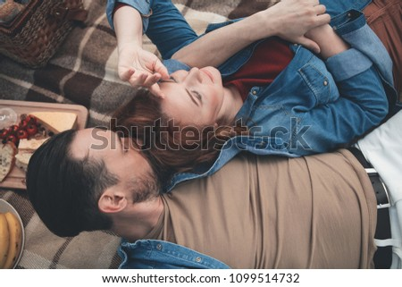 I will always love you. Affectionate man is kissing head of his wife with love. Woman is lying near him on blanket and relaxing outdoor. Top view  #1099514732