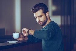 I will be in time. Handsome young man checking time on his wristwatch and holding coffee cup while sitting at bar counter