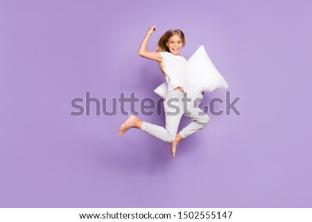 I win pillow fight game! Full body photo of funny funky blonde hair child jump show biceps feel fun funny funky enjoy sleep-over weekends wear white t-shirt pants isolated violet color background