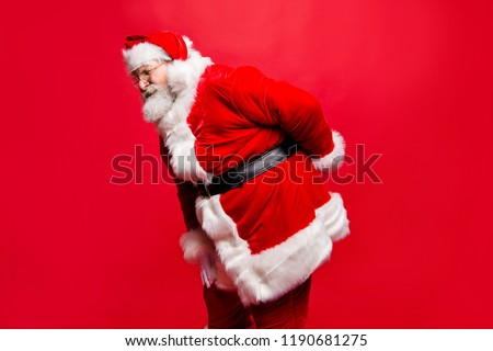 I wish visit chiropractor! Profile side view stylish aged unhealthy spine mature Santa in costume headwear gloves with scoliosis pose with cramp spasm or injury in back isolated noel red background #1190681275