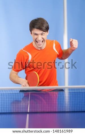 I won! Happy young men gesturing with a table tennis racket in his hand