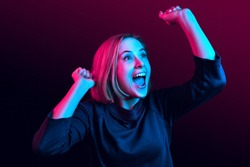I won. Winning success happy woman celebrating being a winner. Dynamic image of caucasian female model on neon studio background. Victory, delight concept. Human facial emotions concept. Trendy colors
