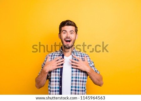 I won?! Young brunette man with an enthusiastic face look into the camera put his hands on his chest and wide open mouth and eyes with surprise isolated on shine yellow background #1145964563
