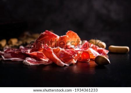 Iberian Ham. acorn-fed Iberian ham. Portion of Iberian ham on slate Photo stock ©