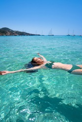 Ibiza bikini girl swimming clear water beach of Balearic Islands