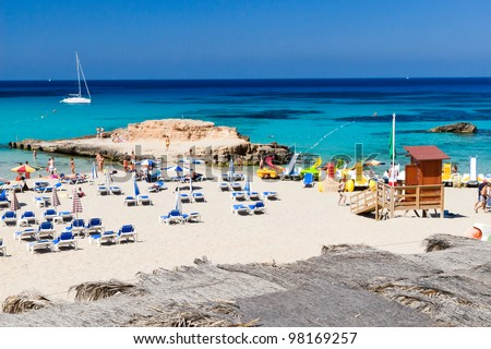IBIZA, SPAIN - JULY 2: Tarida beach at sunny hot weather in Ibiza, Spain on July 2, 2007. Ibiza island is famous summer vacation and entertainment destination for young people. - stock photo