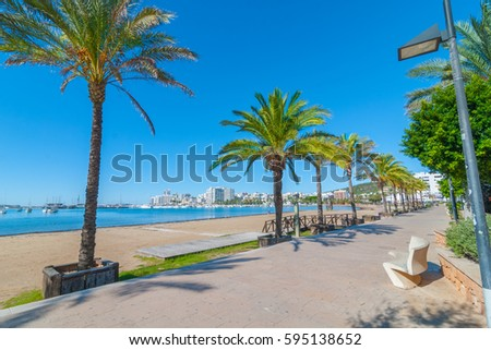 Ibiza sun on the waterfront in Sant Antoni de Portmany,  Take a walk along main boardwalk, now a stone concourse, beside the beach in warm morning sunshine.  Lovely palm tree lined route.
