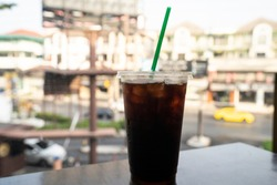 ice americano on table at window and city background