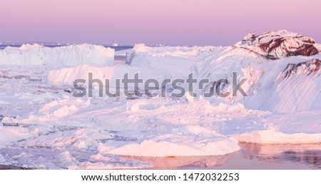Ice and Icebergs from glacier - amazing arctic nature landscape aerial image of icefjord filled with icebergs from melting glacier Sermeq Kujalleq, Ilulissat, Greenland. Midnight sun.