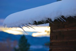 Ice and Snow hanging over roof edge of barn in Western Montana
