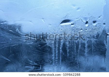 Ice and water drop on winter glass