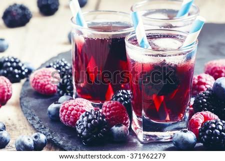 Ice berry tea with raspberries, blackberries and blueberries, selective focus