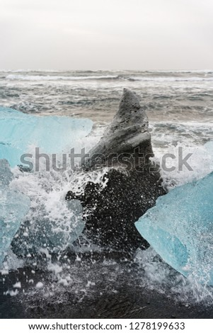 Ice blocks in blue and dark shades on a black beach with strong surf, spray of a wave splashes over the ice, waves roll in the background - Location: Iceland, Jökulsarlon (Jökulsárlón) #1278199633